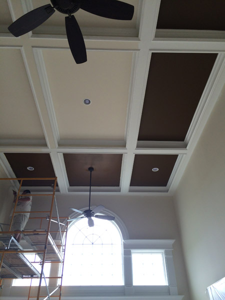 Painters on scaffolding painting a coffered ceiling.