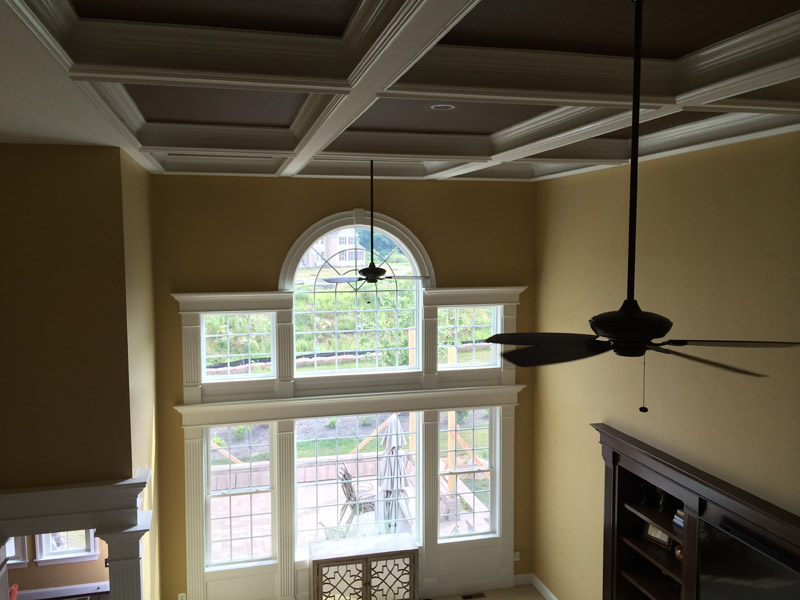 Completed great room with a brown paint accented coffered ceiling